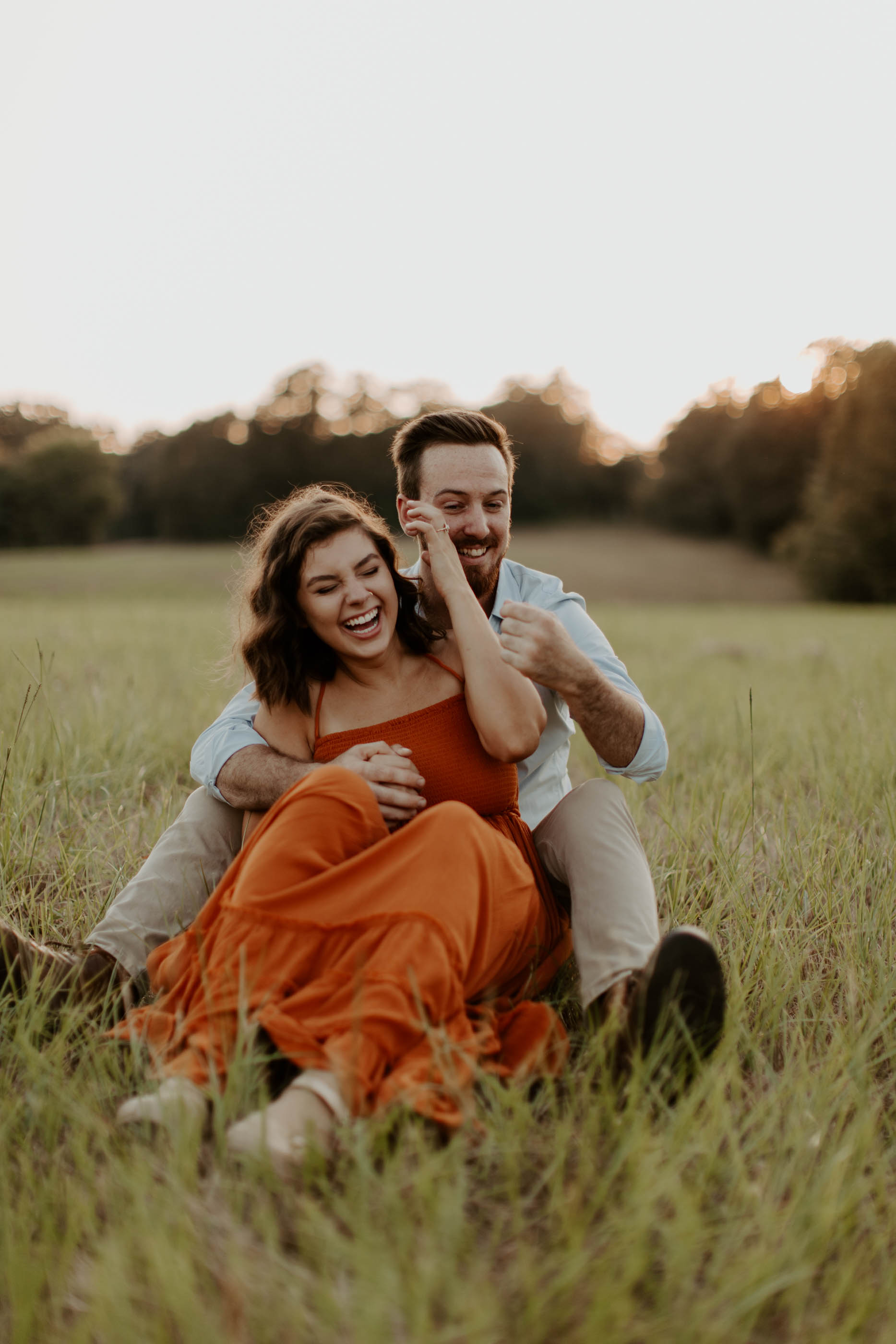 couple sitting in grass laughing