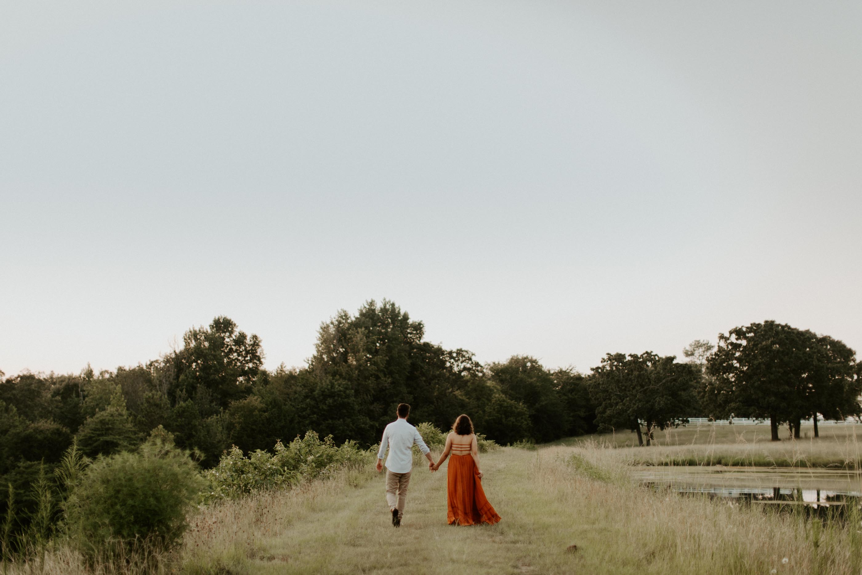 engaged couple walking on path in field