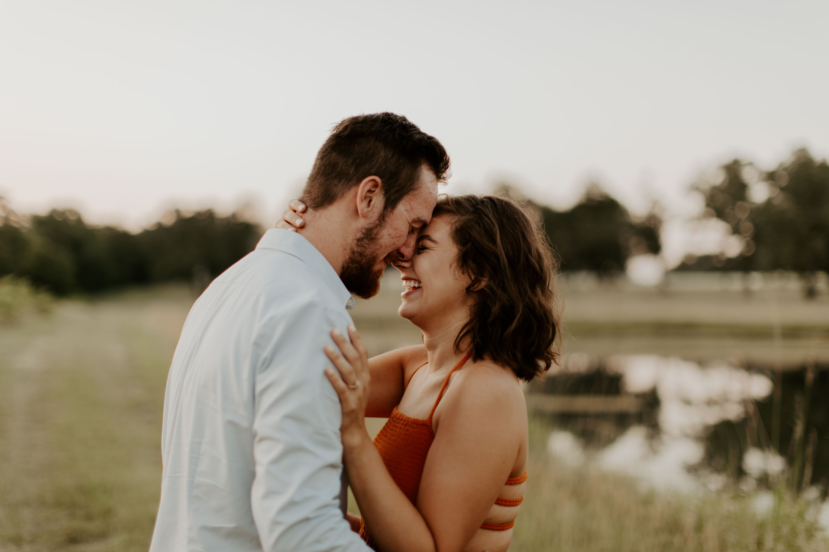 couple laughing and being romantic in front of lake