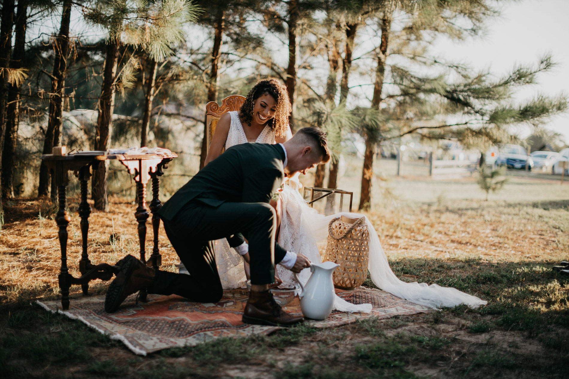 Groom washing brides feet during boho wedding ceremony