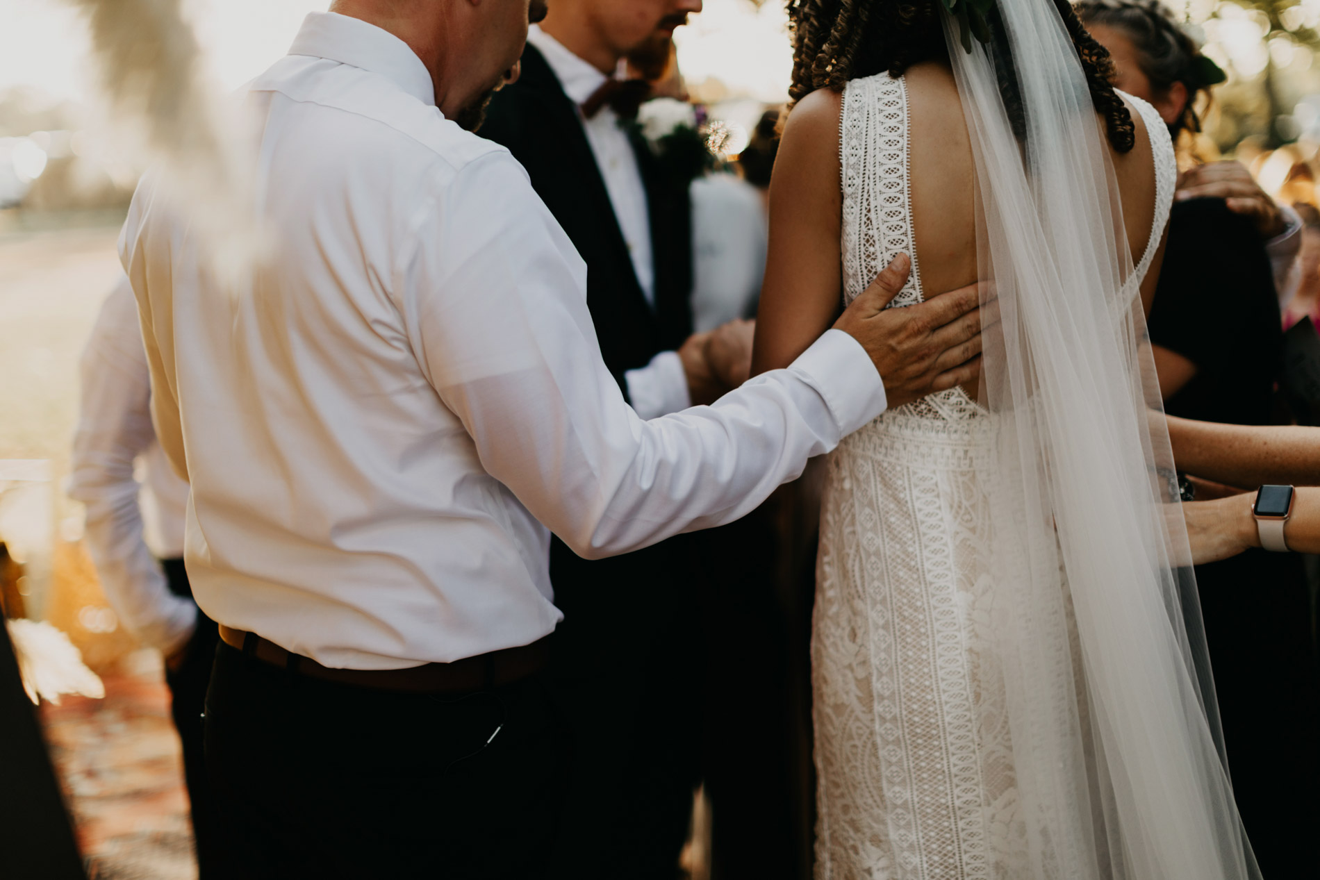 Pastor praying over bride and groom on wedding day