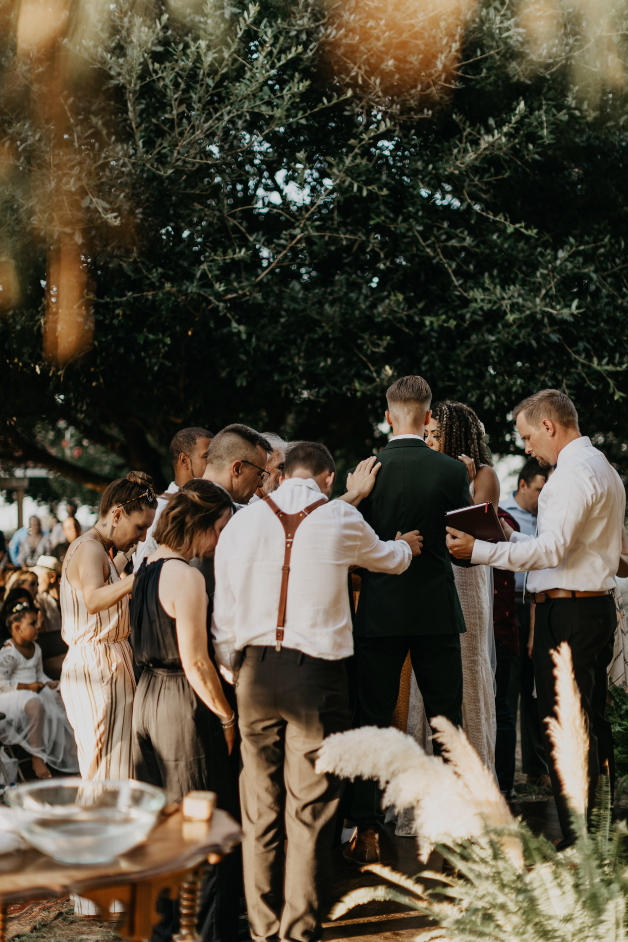 Bride and groom praying with family on wedding day