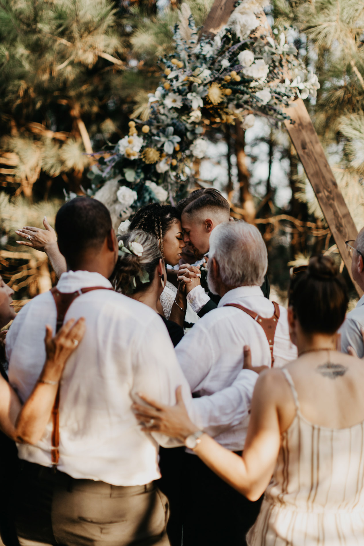 Bride and grooms family praying over them on wedding day
