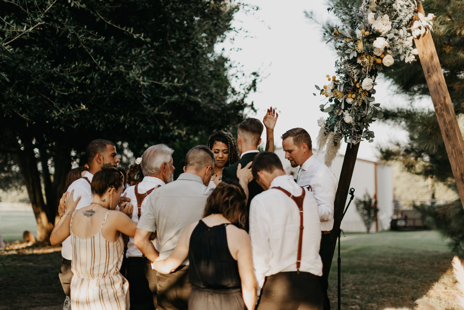 Family worshiping with bride and groom during wedding ceremony