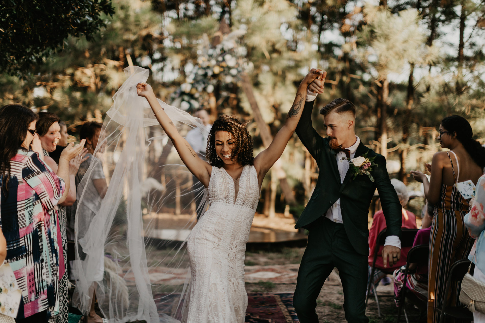 Boho bride and groom dancing down the aisle