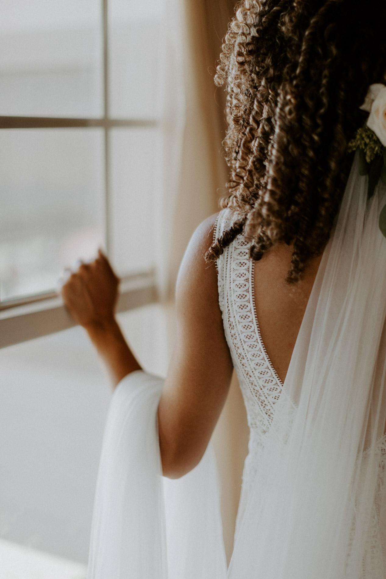 Bride looking out window as she is getting ready for her wedding