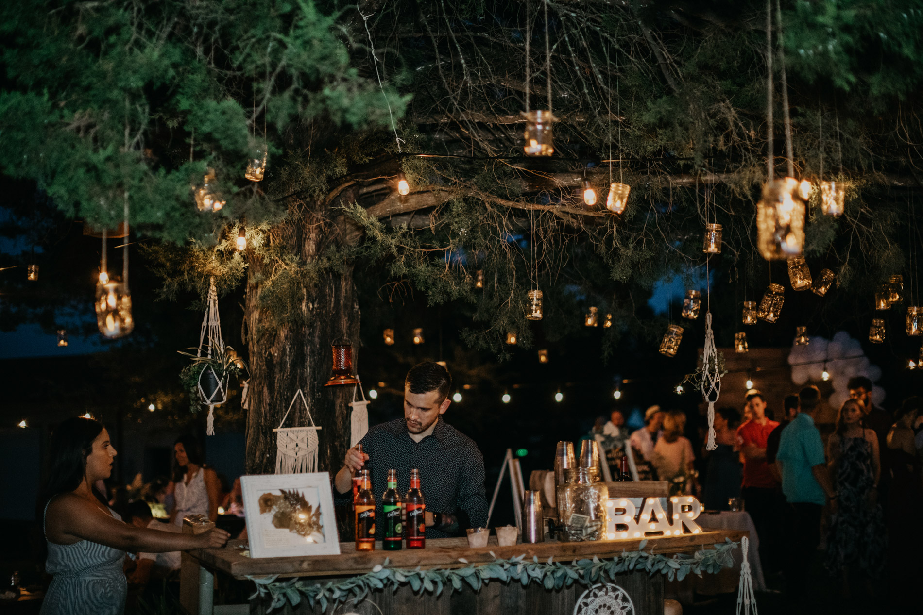 Adorable bohemian wedding bar with a lot of string lights