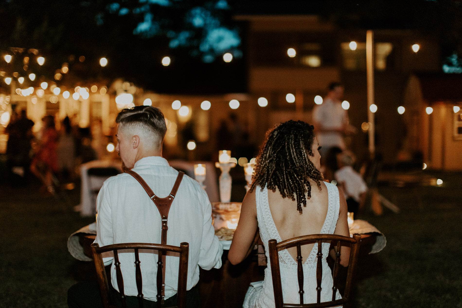 Bride and groom eating dinner at their bohemian wedding reception