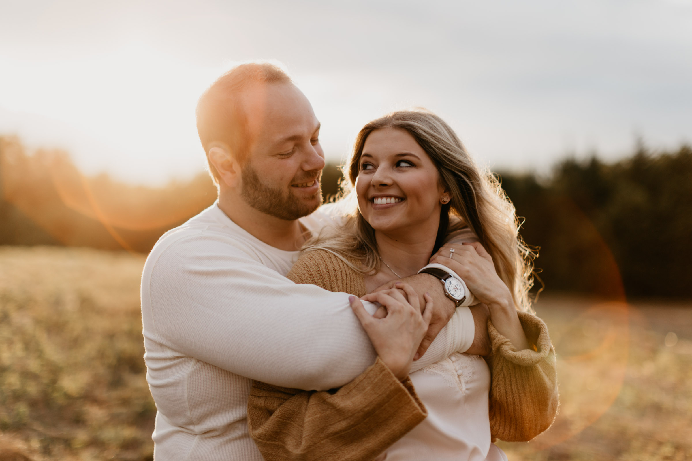 Couple being romantic at golden hour for their engagement session during fall