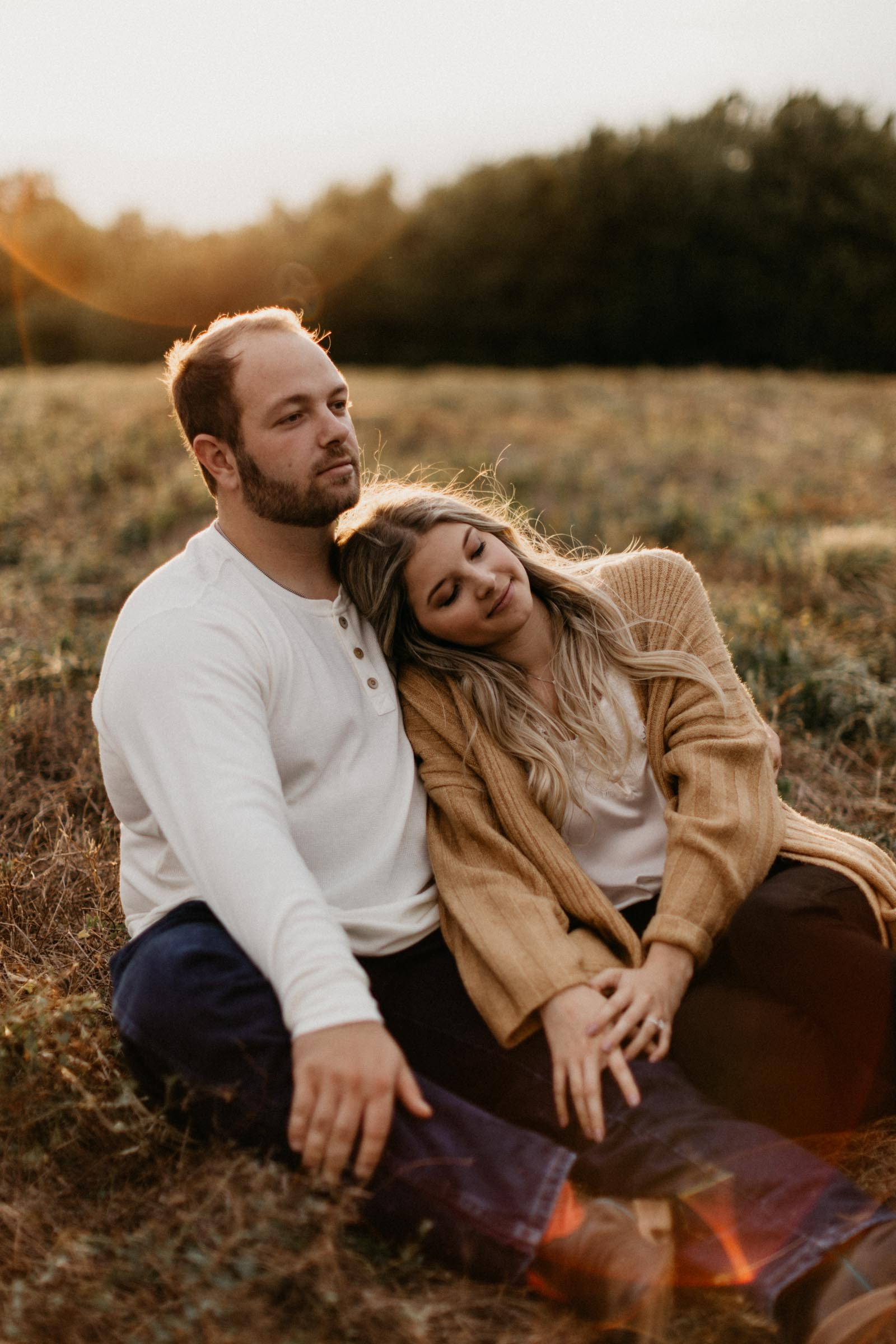 Boy and girl sitting in the grass during golden hour cuddling during fall