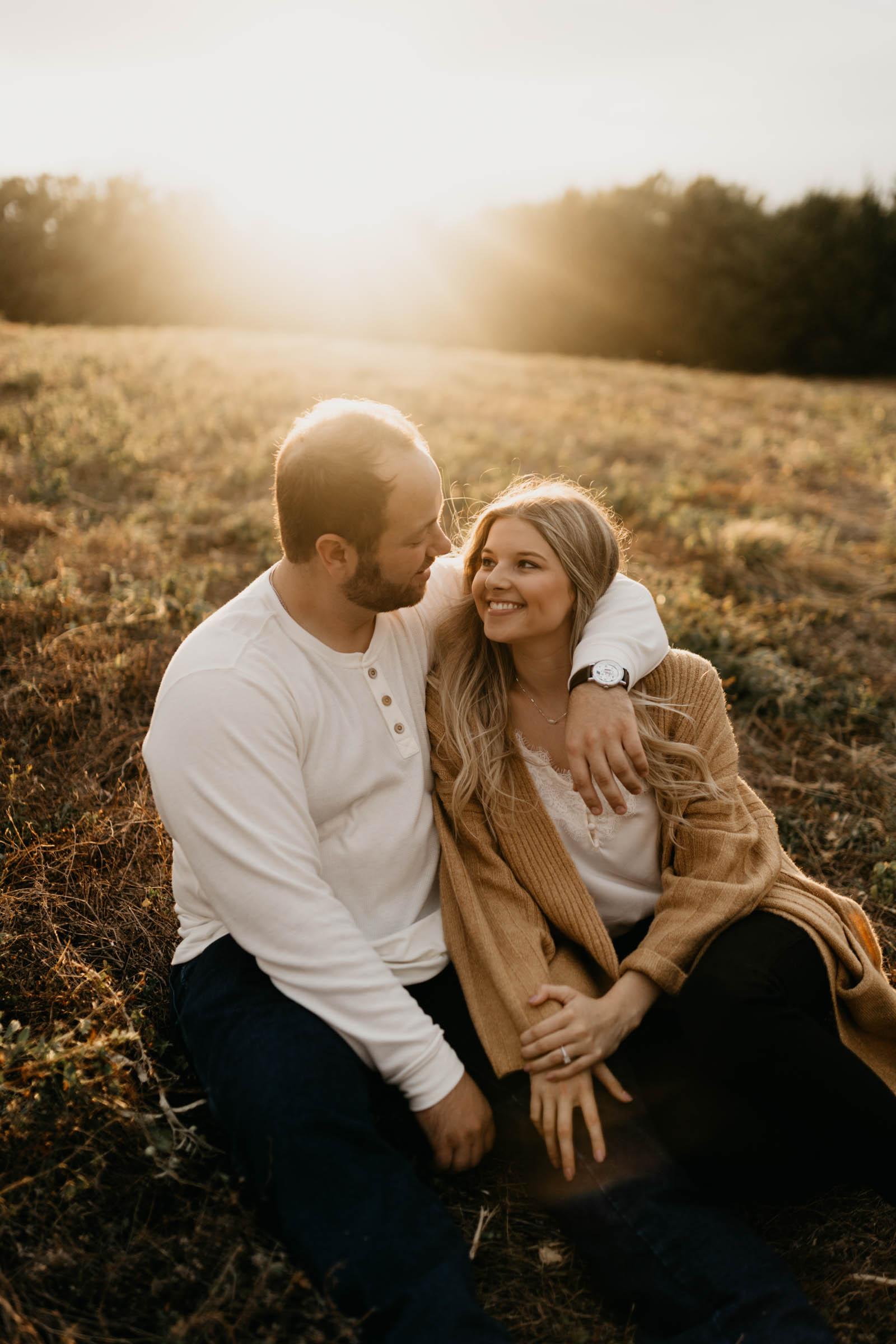 Golden hour engagement session with cuddly couple sitting and being romantic