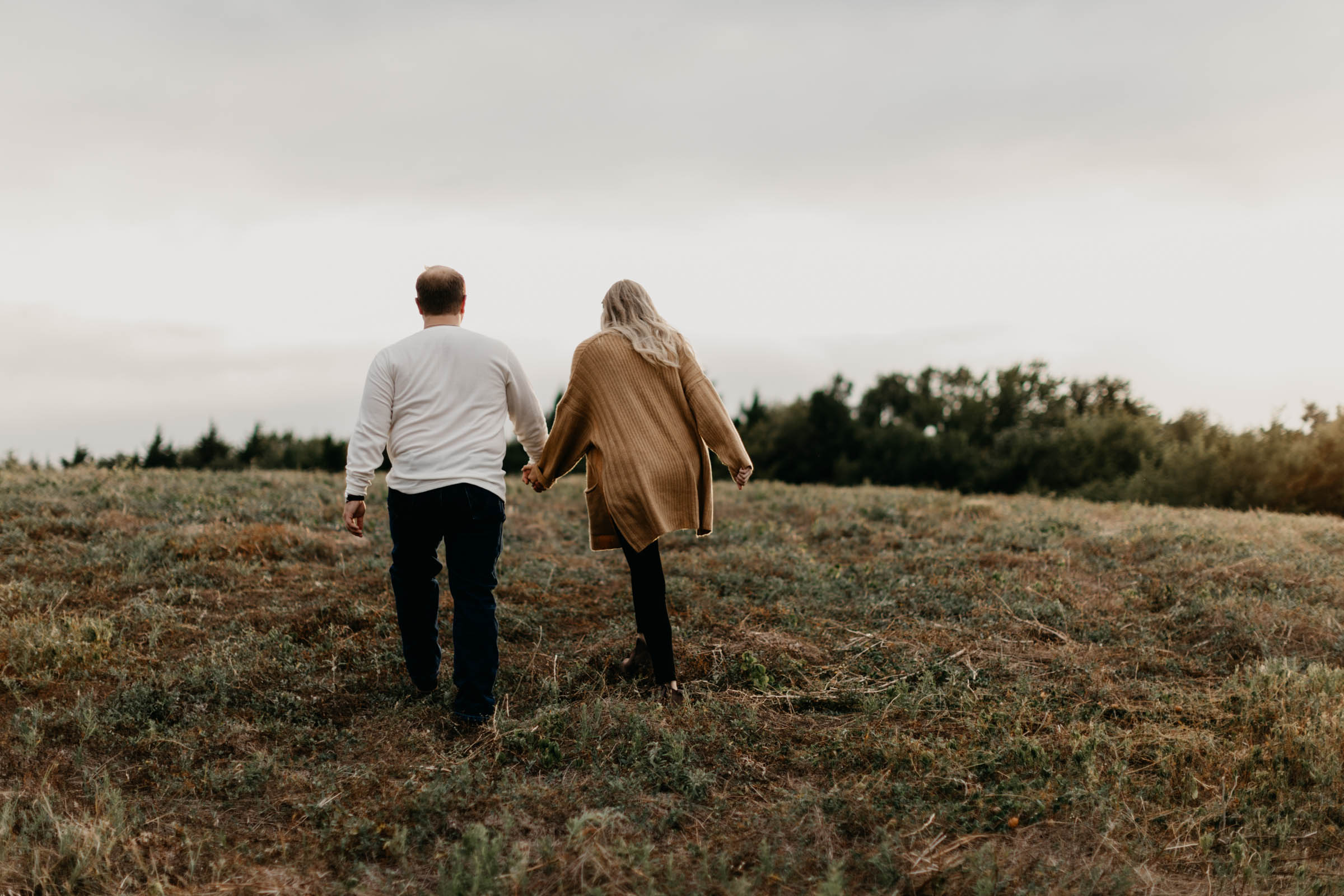 Couple holding hands and walking up a hill during their fall engagement session