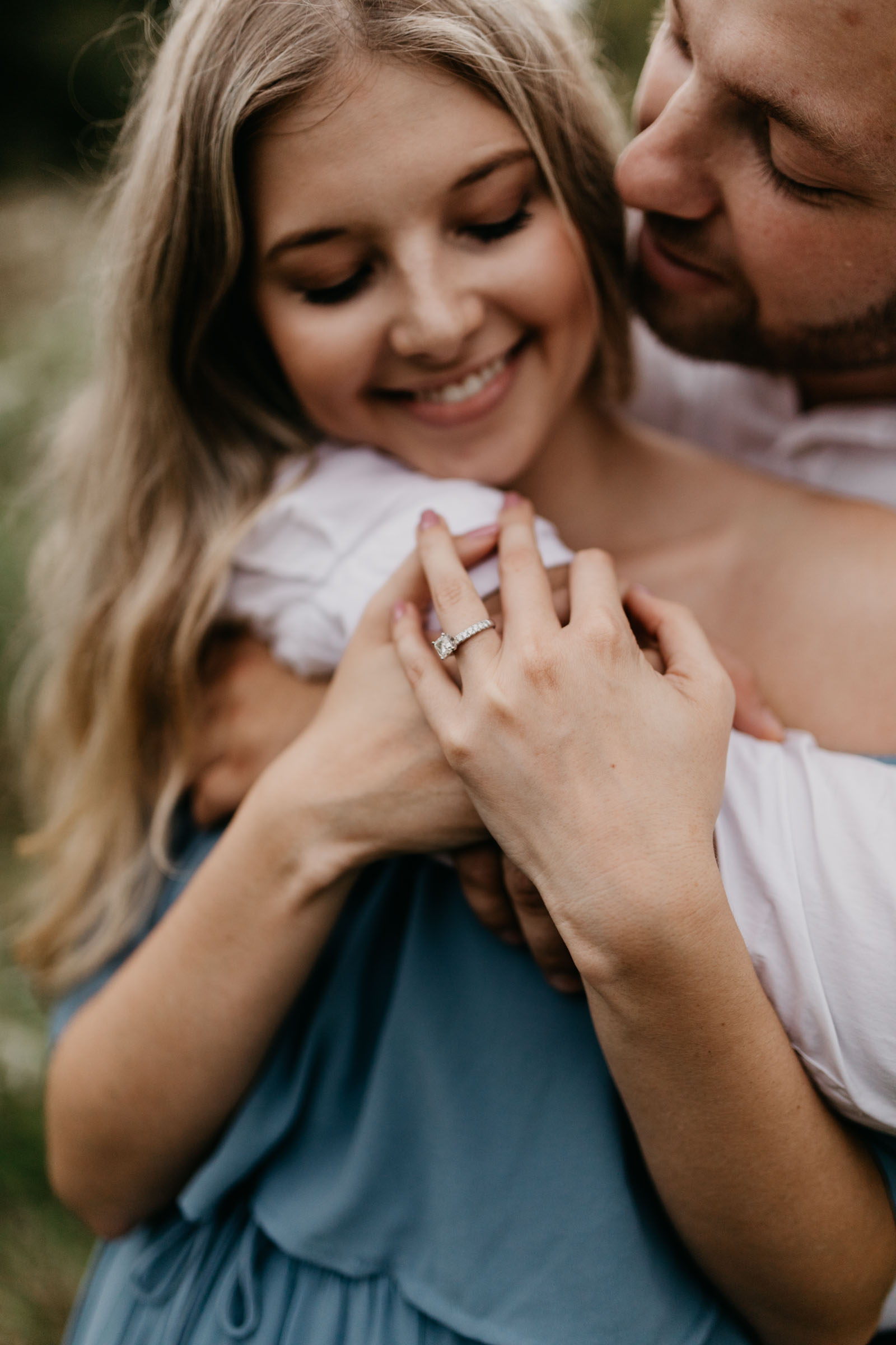 beautiful engagement ring being shown off by adorable couple during their fall photo session
