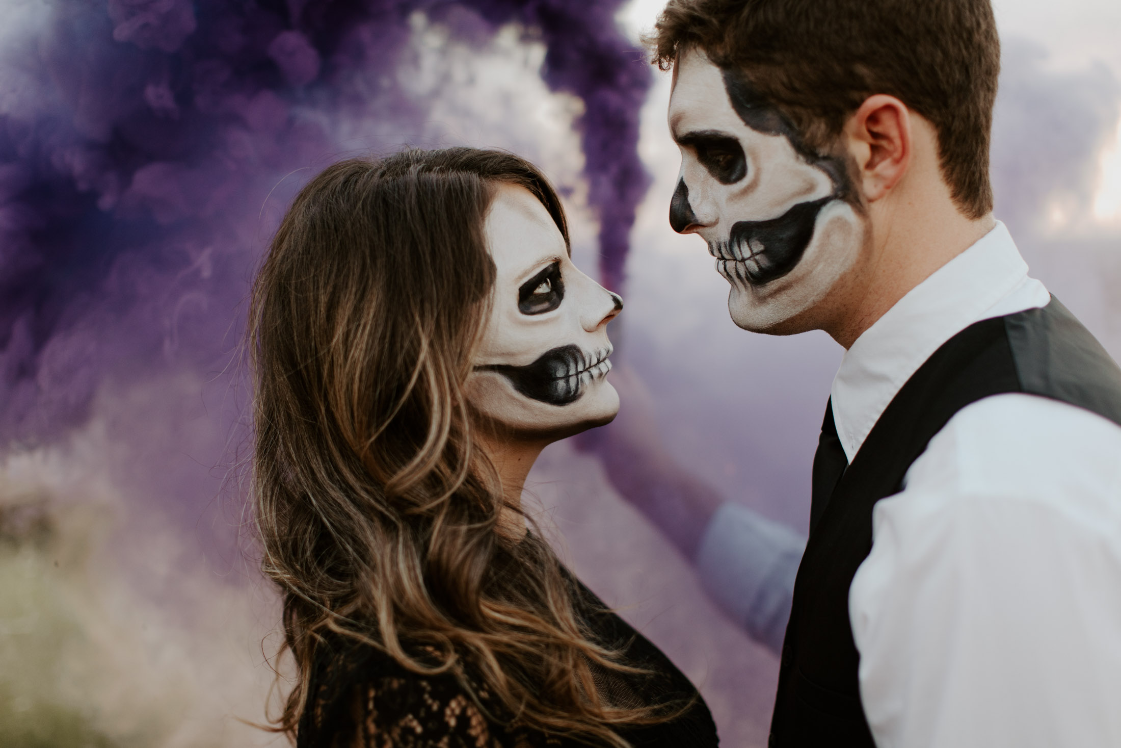 groom holds purple smoke bomb at a halloween themed couples shoot
