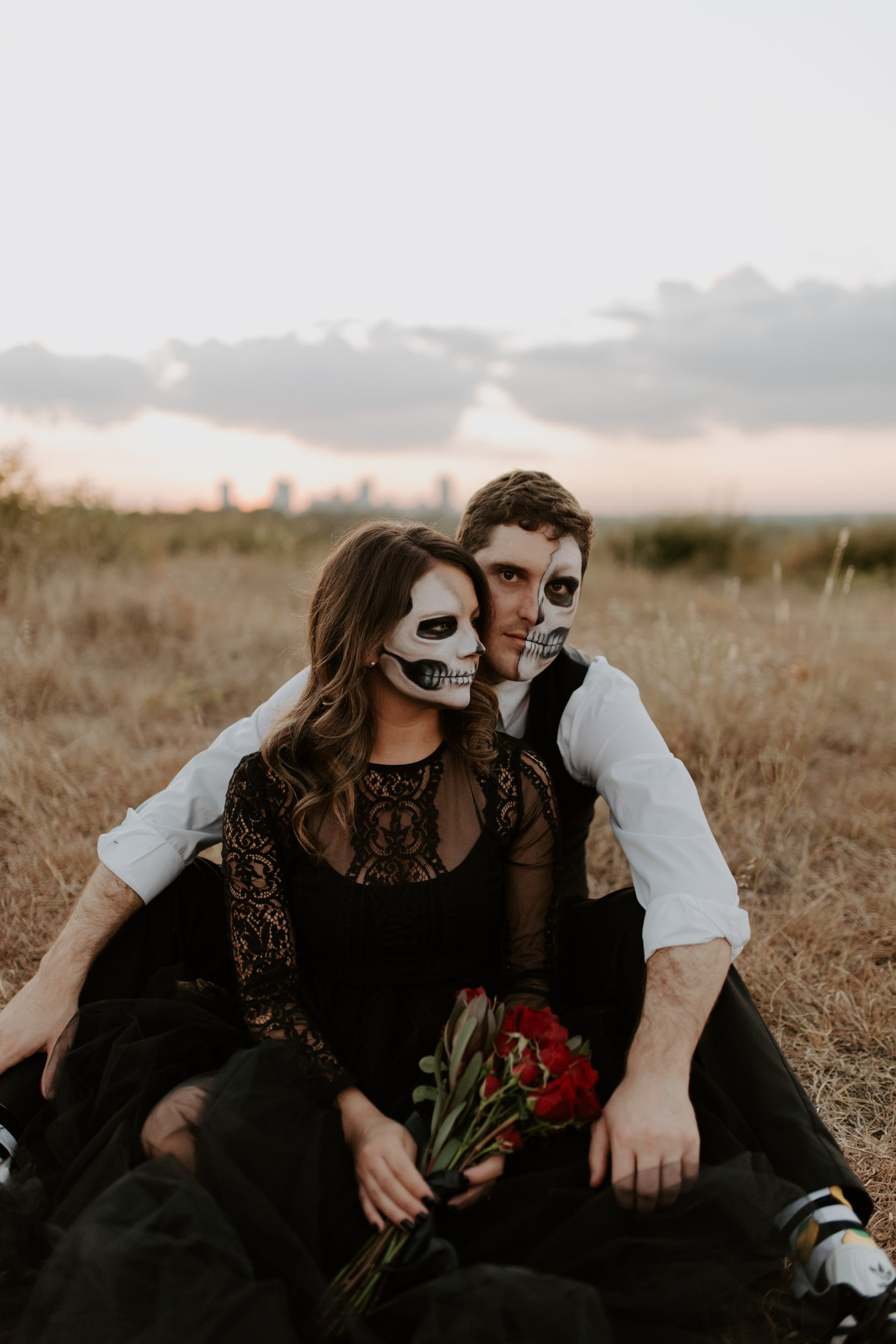 gothic couple with skull makeup sitting in field for a halloween inspired shoot