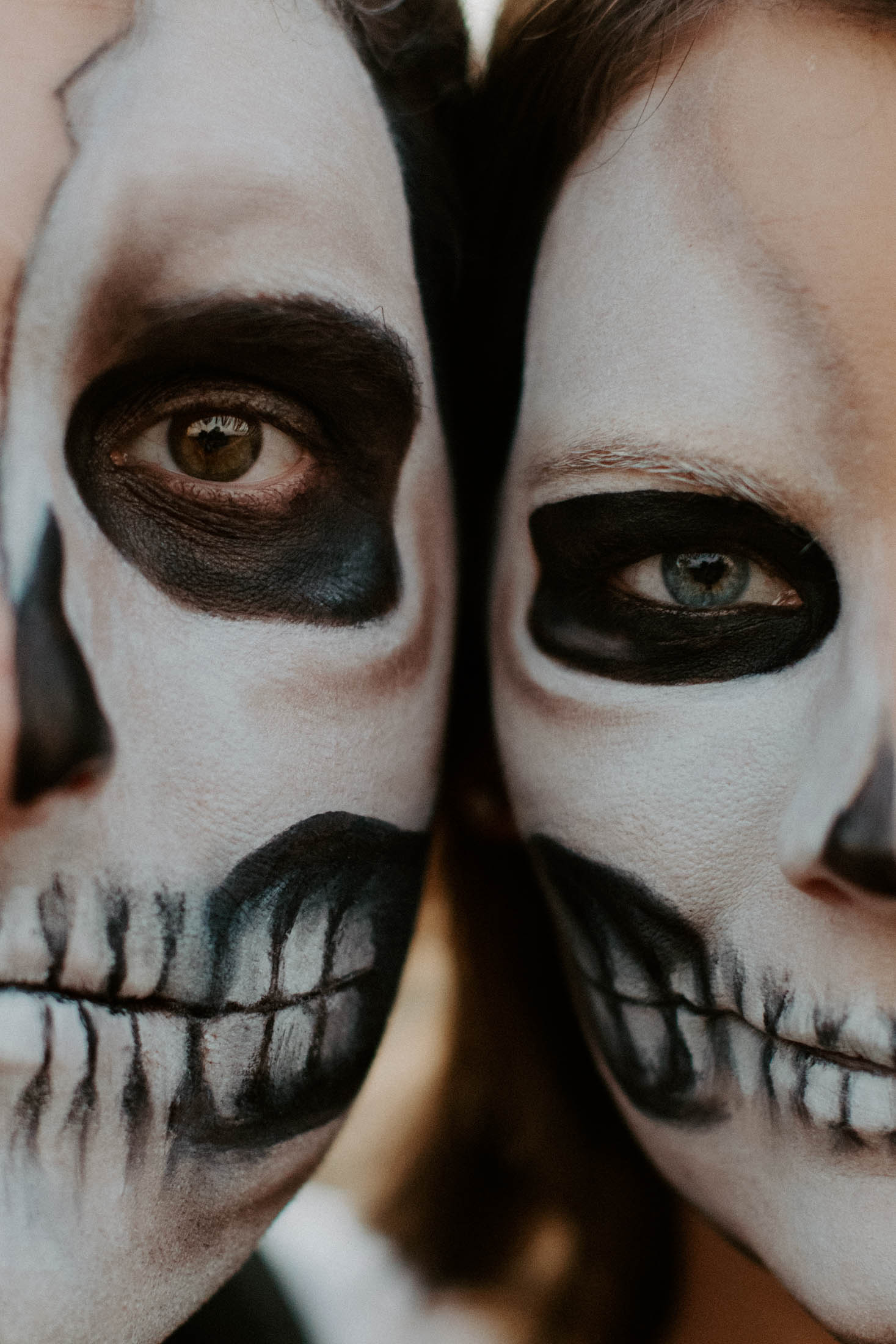 couple wearing skull makeup for halloween photography session sitting next to each other