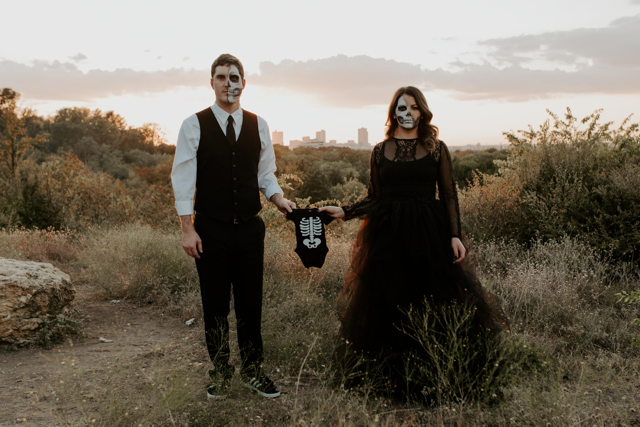 couple in skull makeup holding a baby onesie as a baby announcement