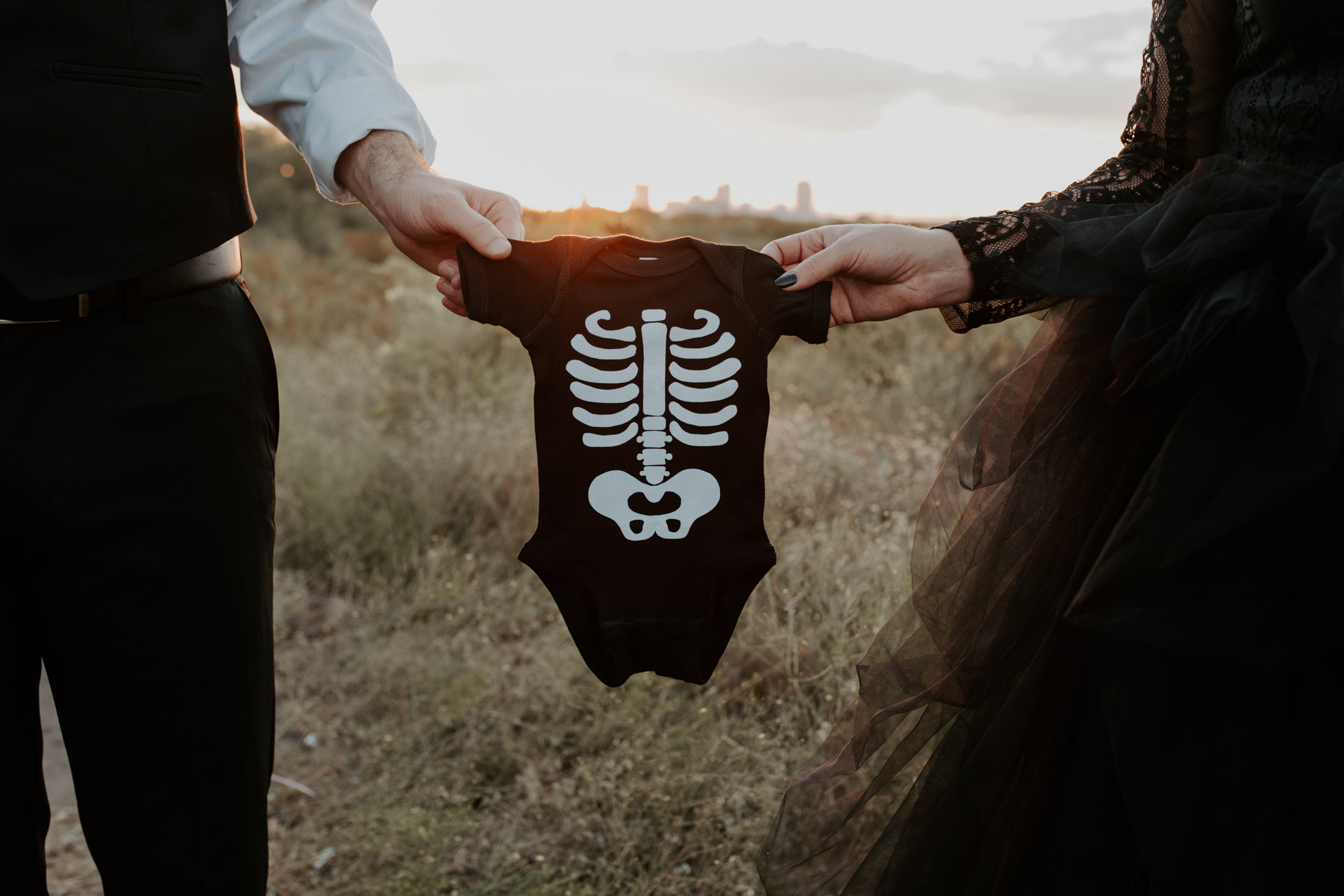 couple holding baby onesie to announce a pregnancy