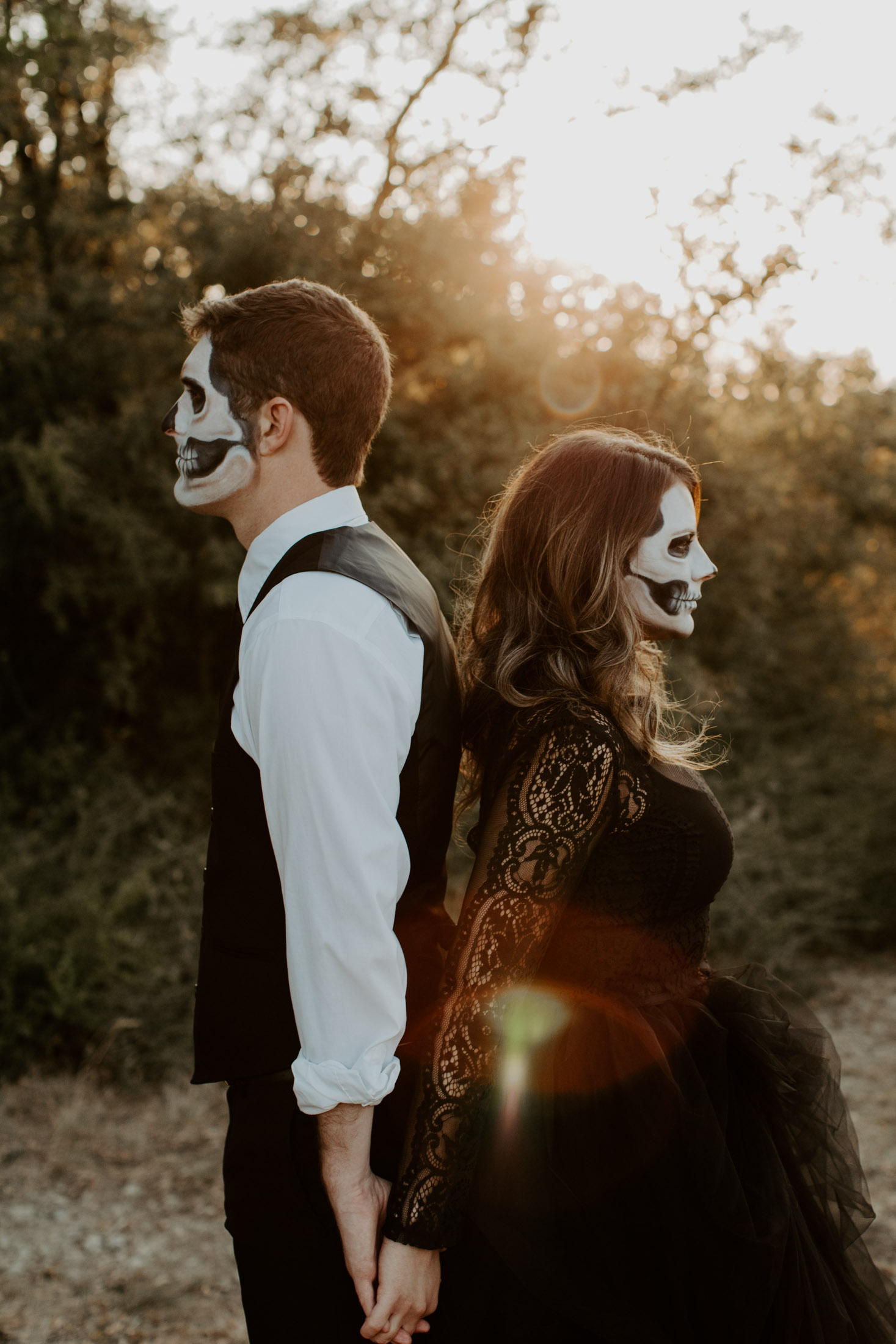 spooky couples session with couple looking in two different directions with skull makeup on