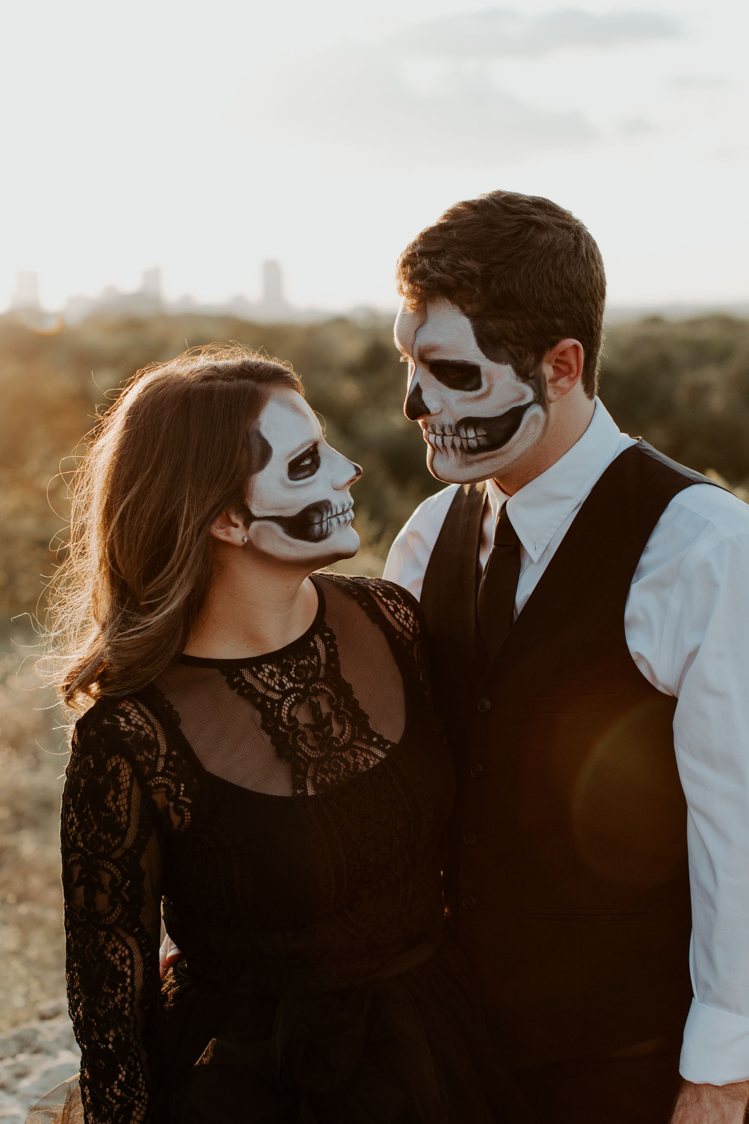 engaged couple looking at each other with skull makeup on for a halloween session