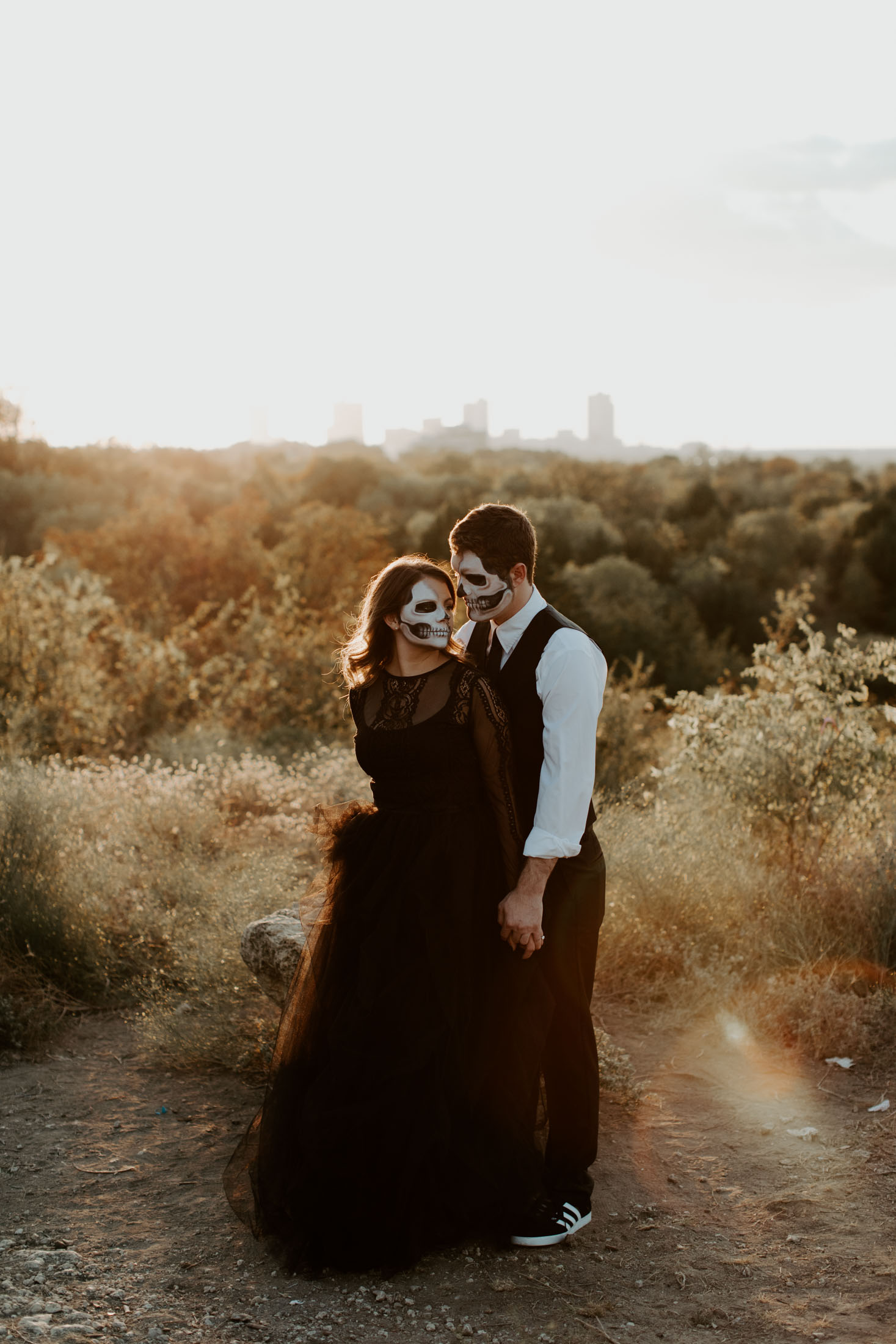 couple on top of a hill in Texas wearing skull makeup for a halloween inspired couples session