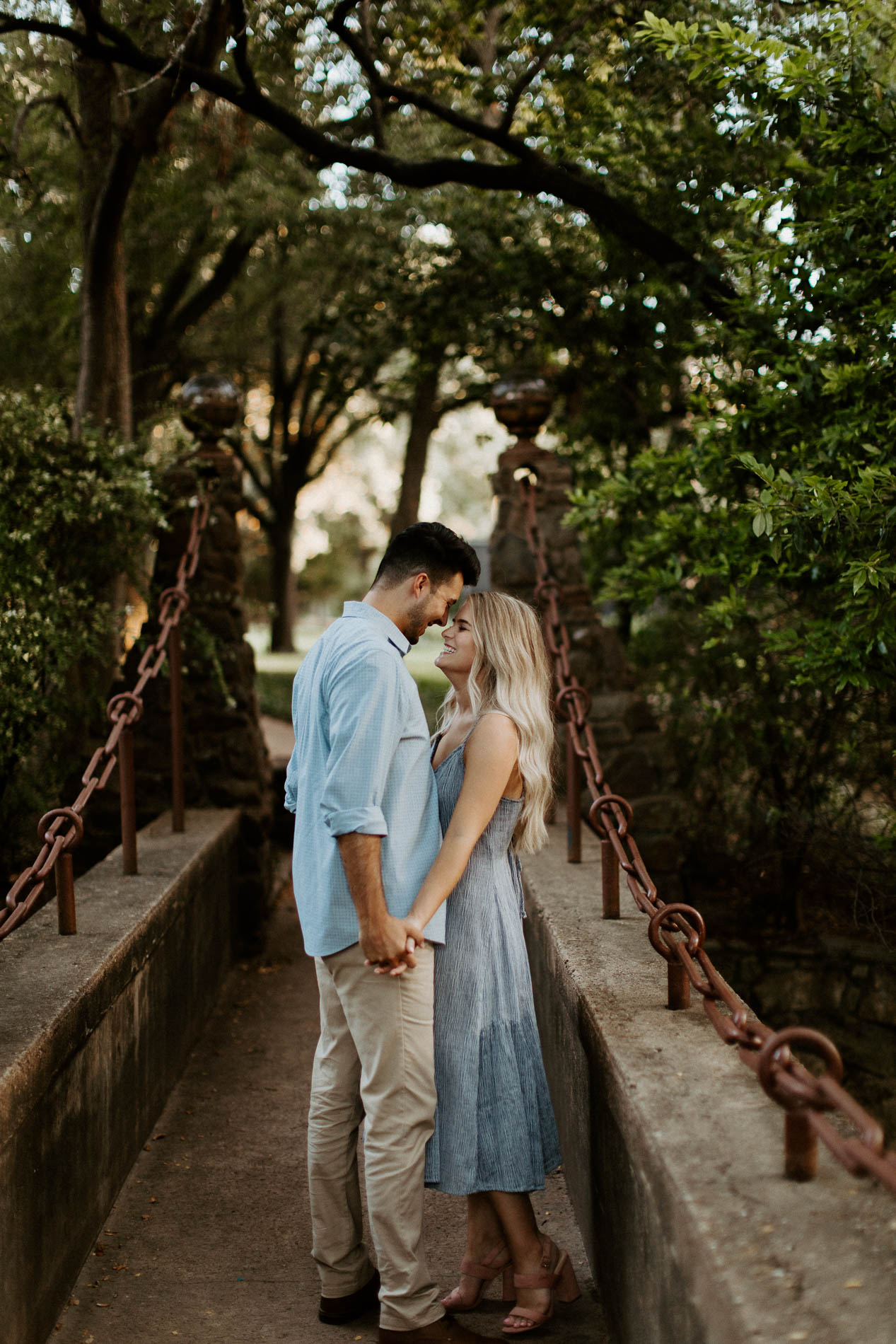 Couple facing each other and being romantic on a rustic bridge in texas