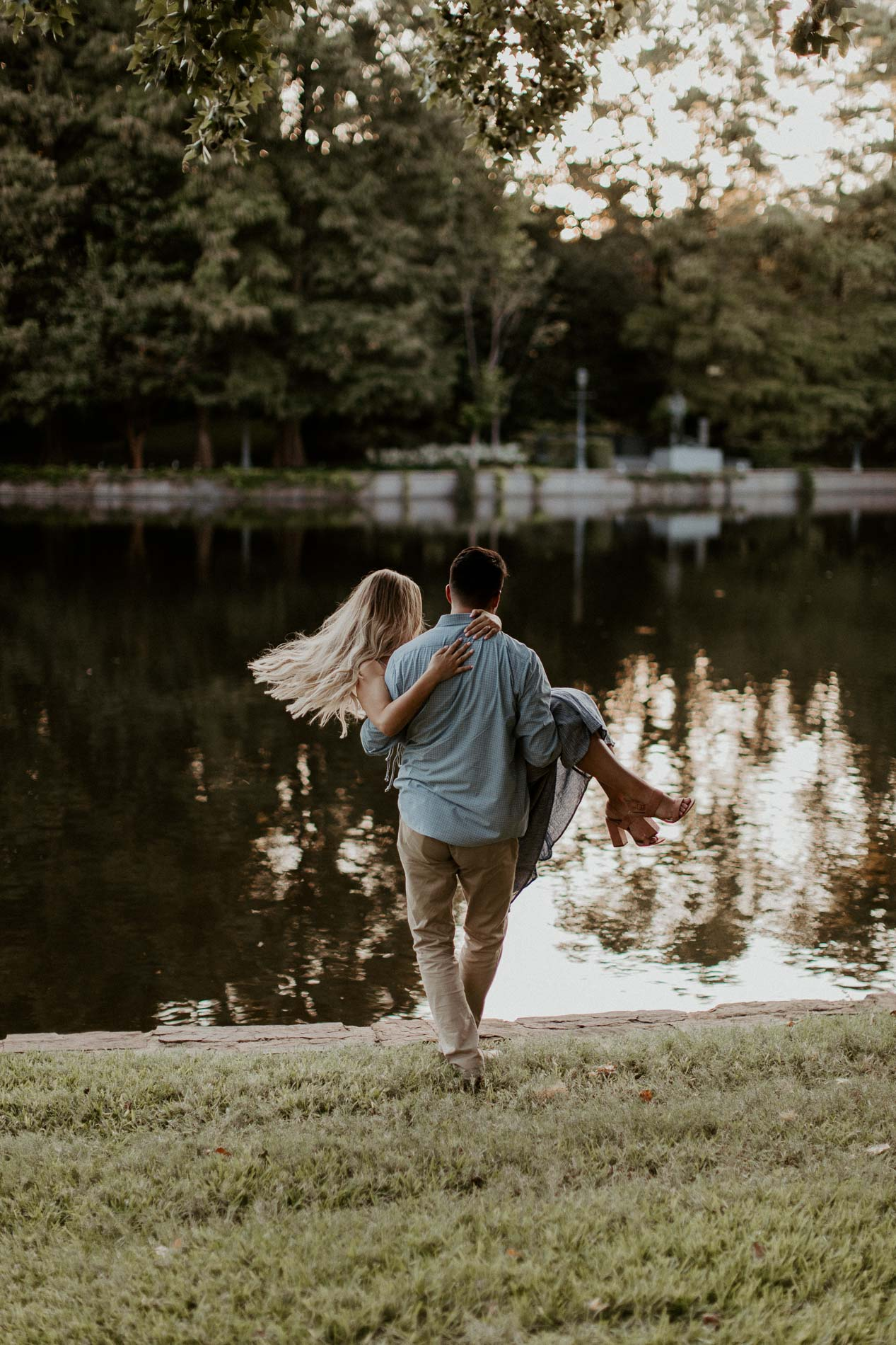 Boy holding girl and walking toward water during a beautiful engagement session location
