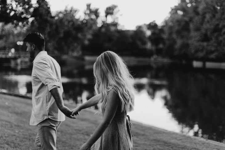 beautiful couple black and white photo during engagement session walking next to a lake