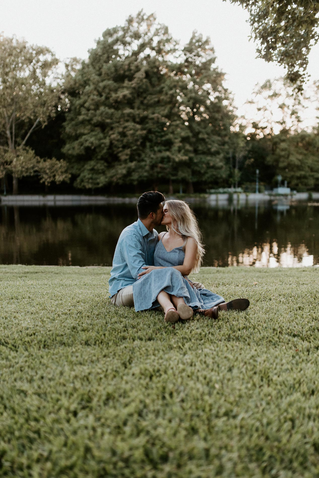 Couple kissing while sitting next to each other on the ground of a park