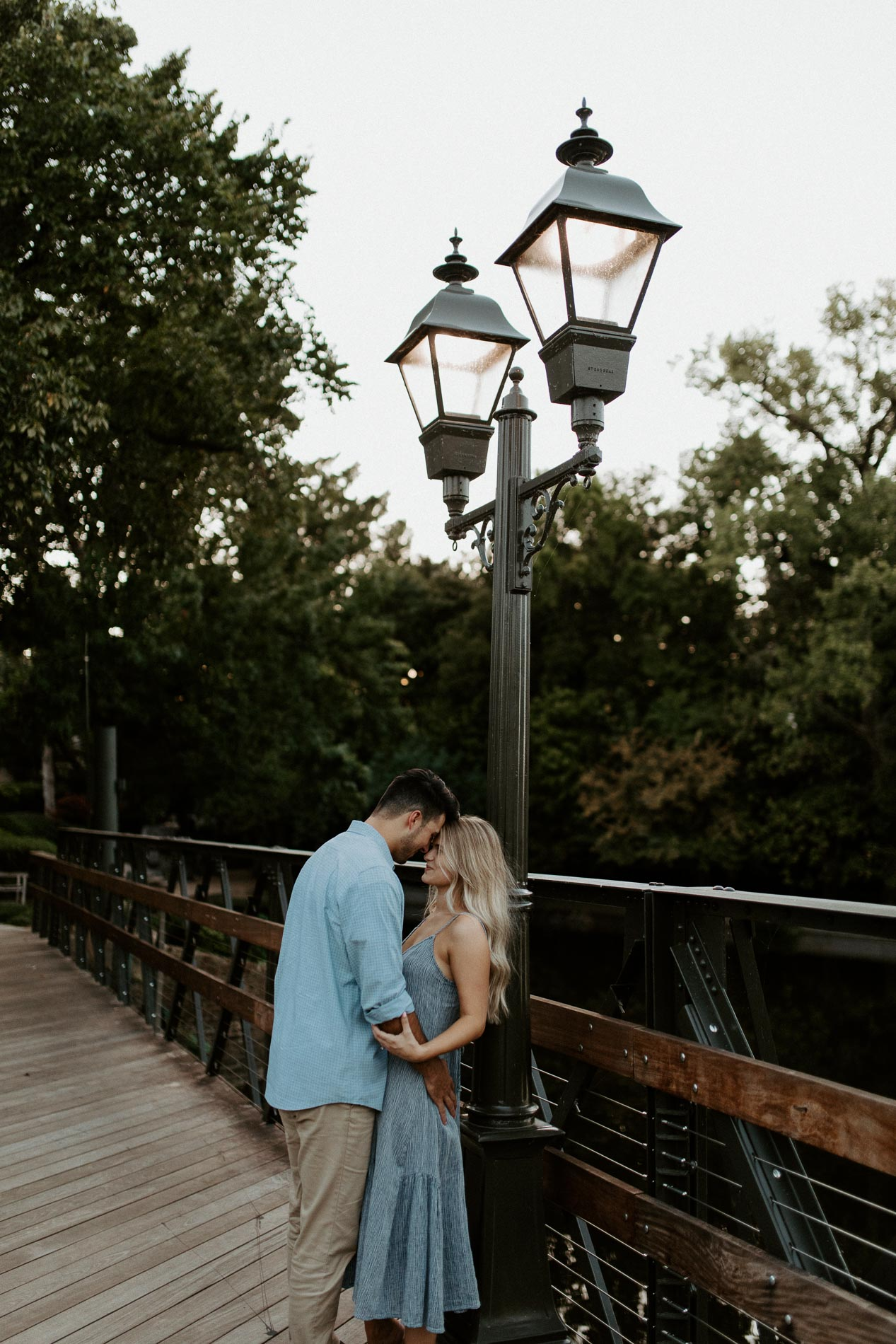 Couple leaning against light pole making out and being romantic for engagement photos