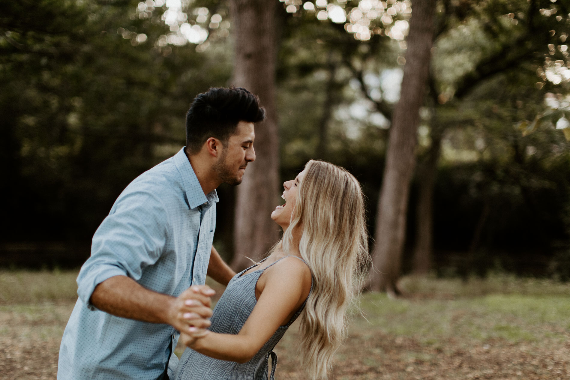 Cute couple laughing during their forest engagement session in north texas