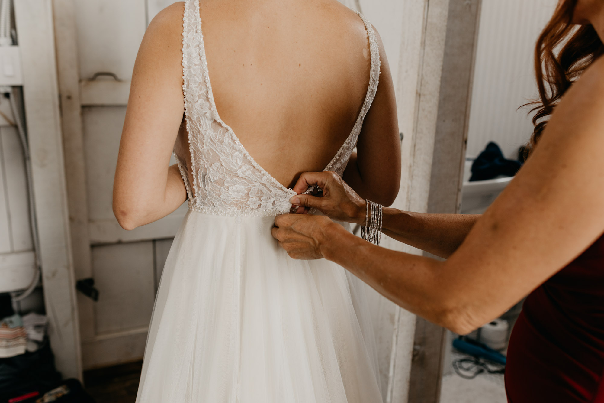 Mother of the bride zipping up brides wedding dress