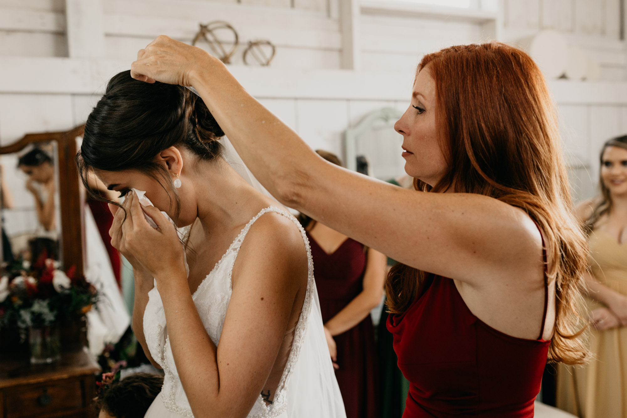 emotional bride crying as mom puts veil in her hair