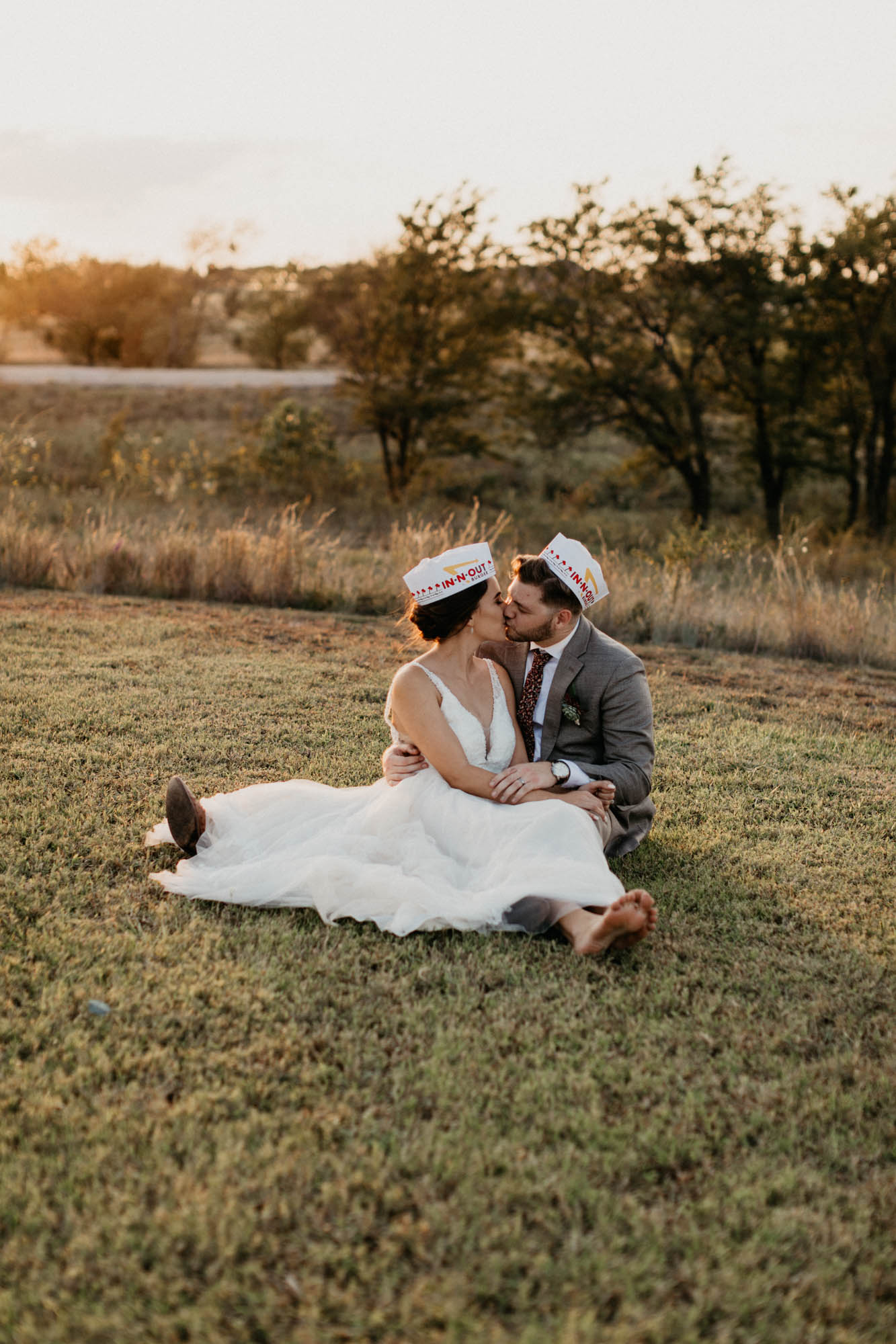 Bride and groom take photo wearing in-n-out hats at their north texas wedding