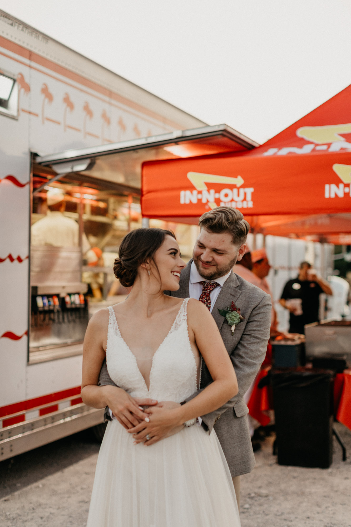 Cute couple takes photo in front of in and out truck on their wedding day