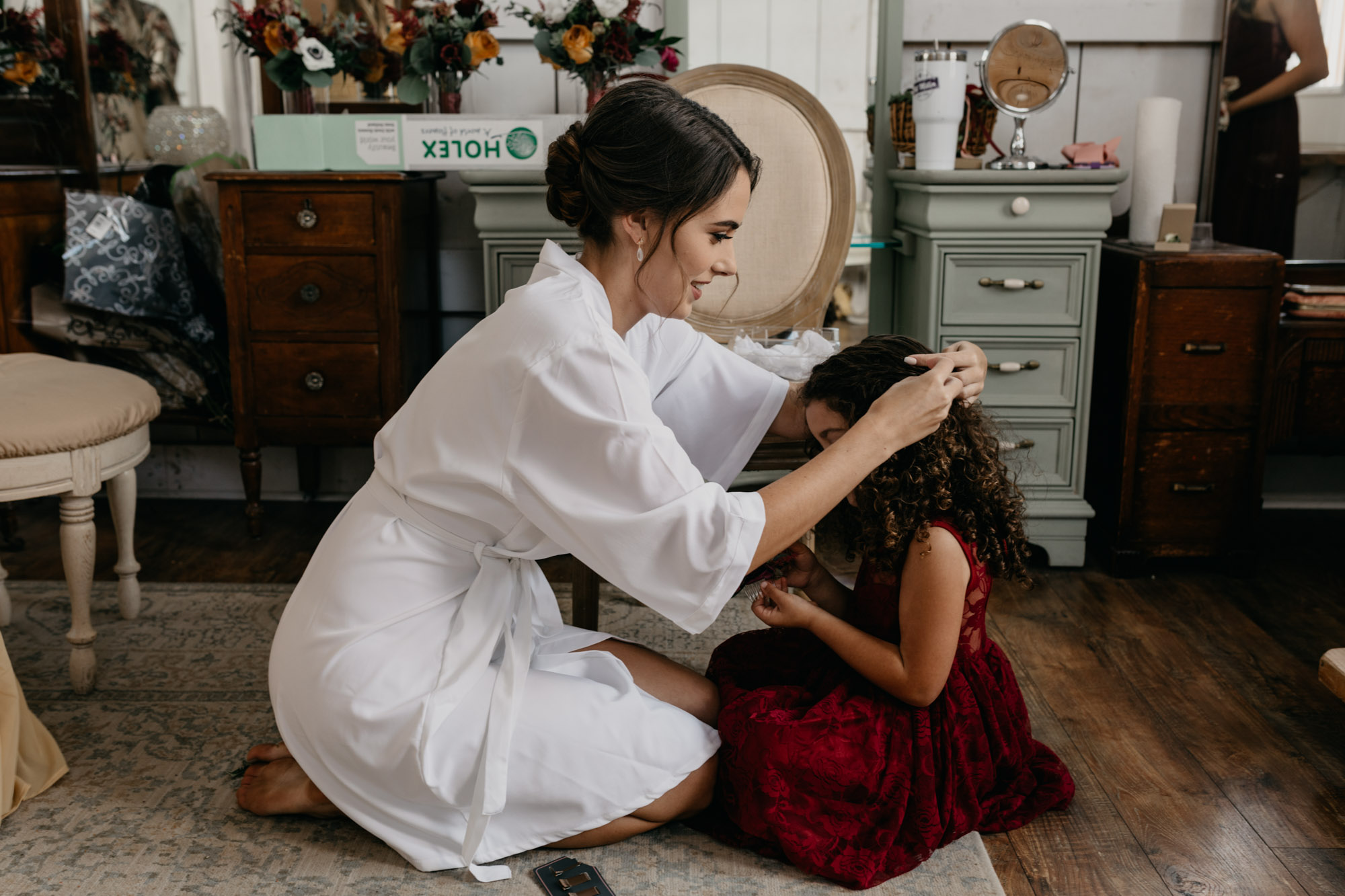 Bride doing flower girls hair in a vintage getting ready room on wedding day