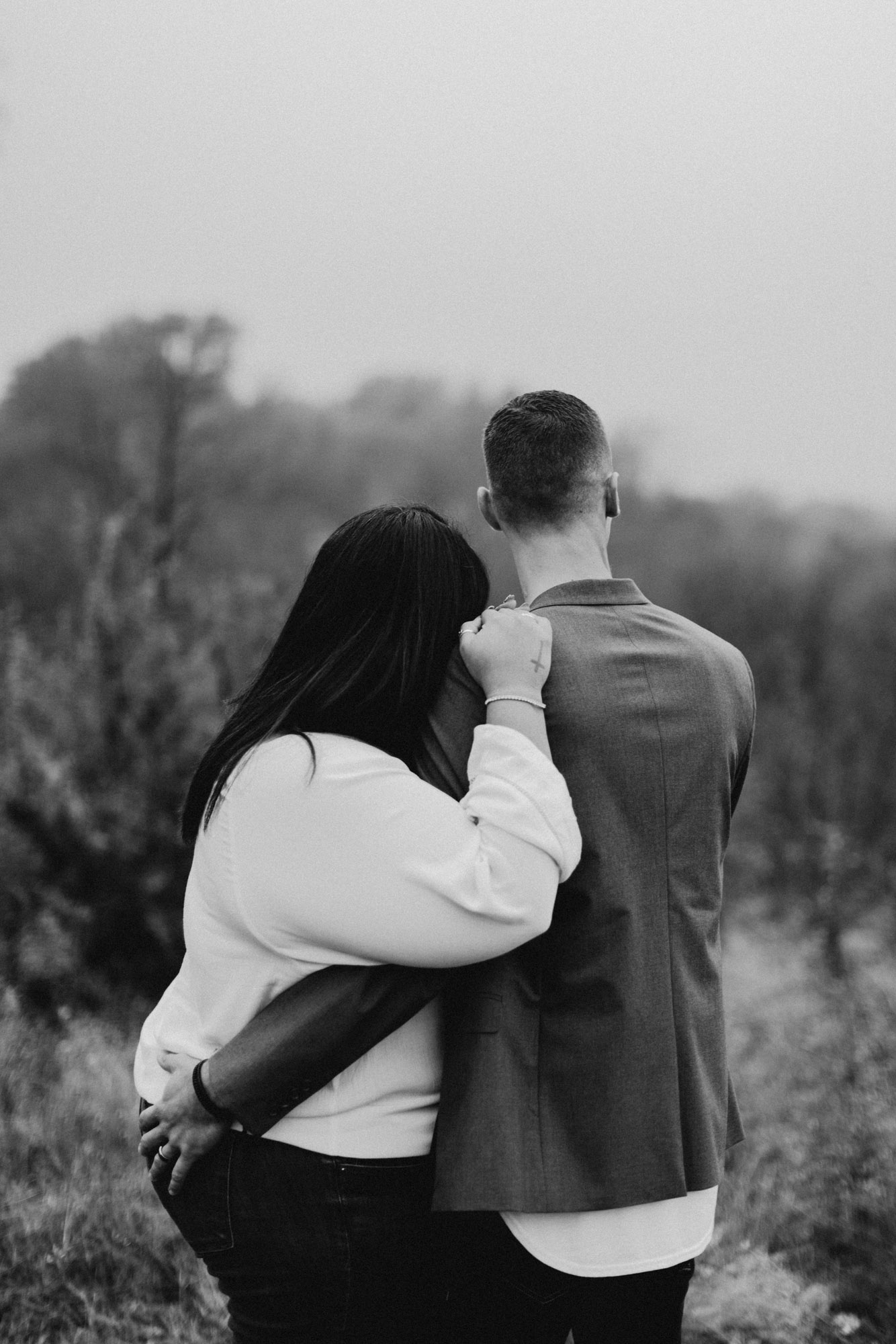 black and white anniversary photo of couple on top of a hill
