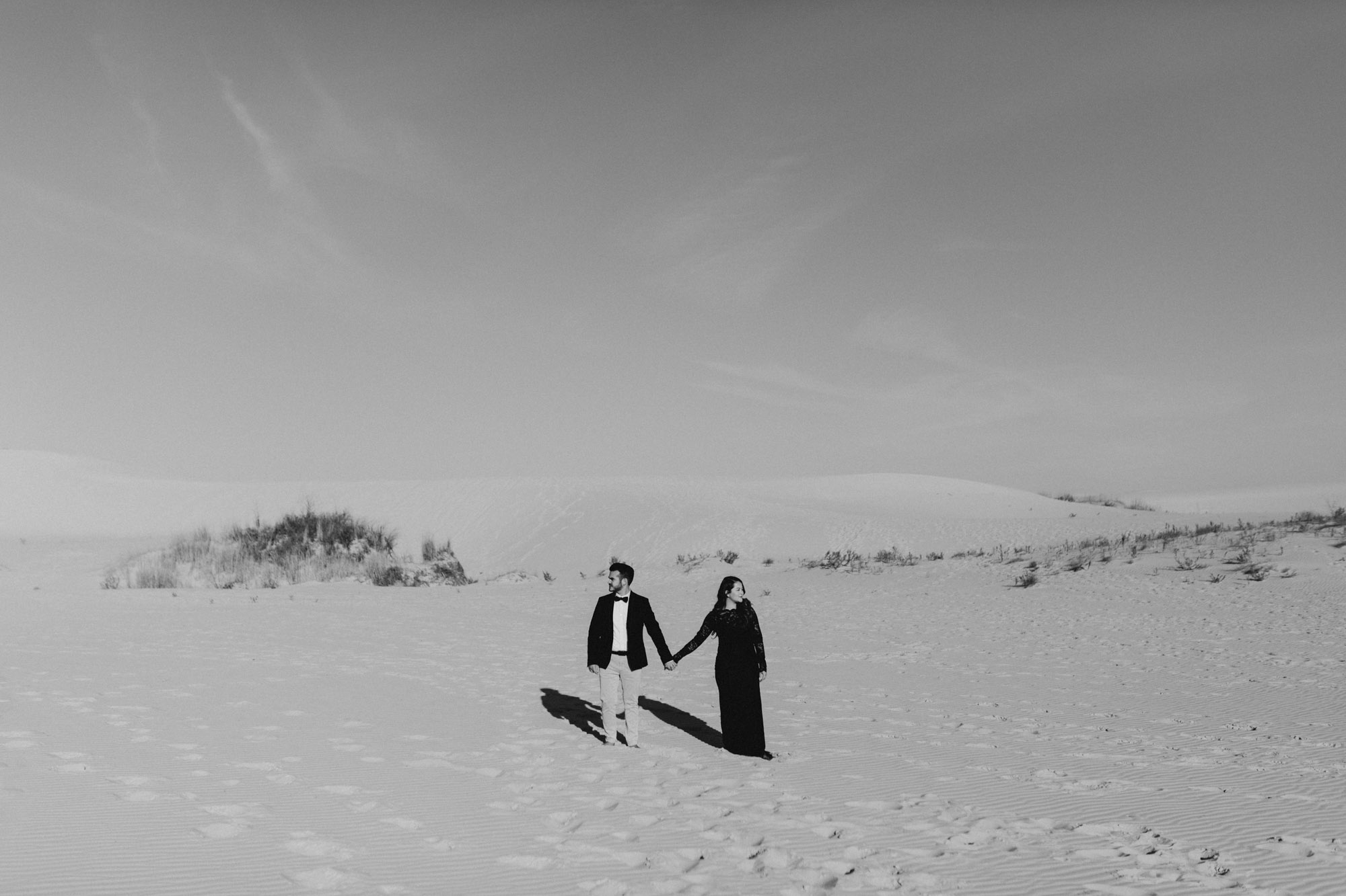 Black and white photo of couple standing side by side at sand hills for an engagement session