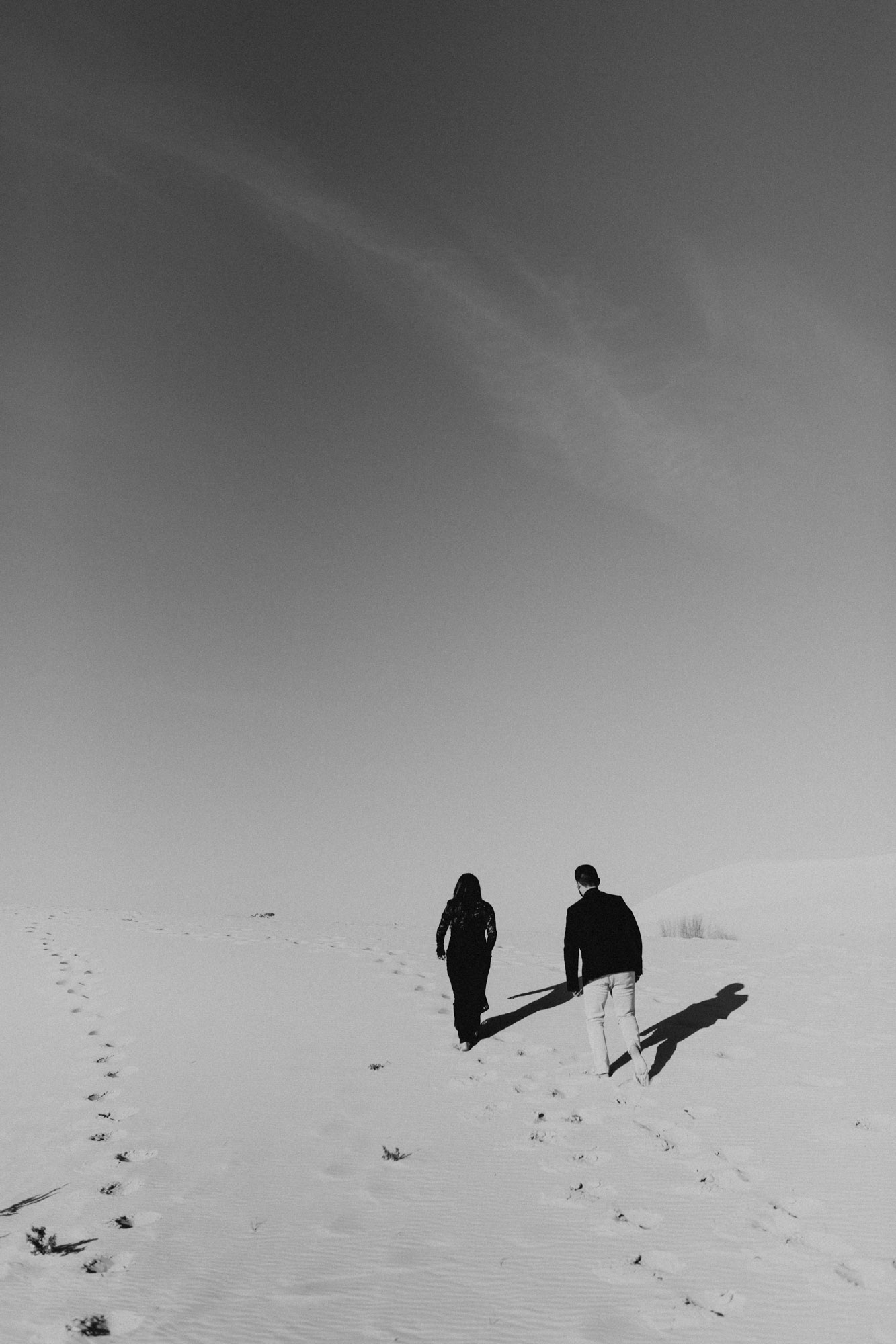 Black and white photo of an adventurous couple exploring sand hills for their engagement photography