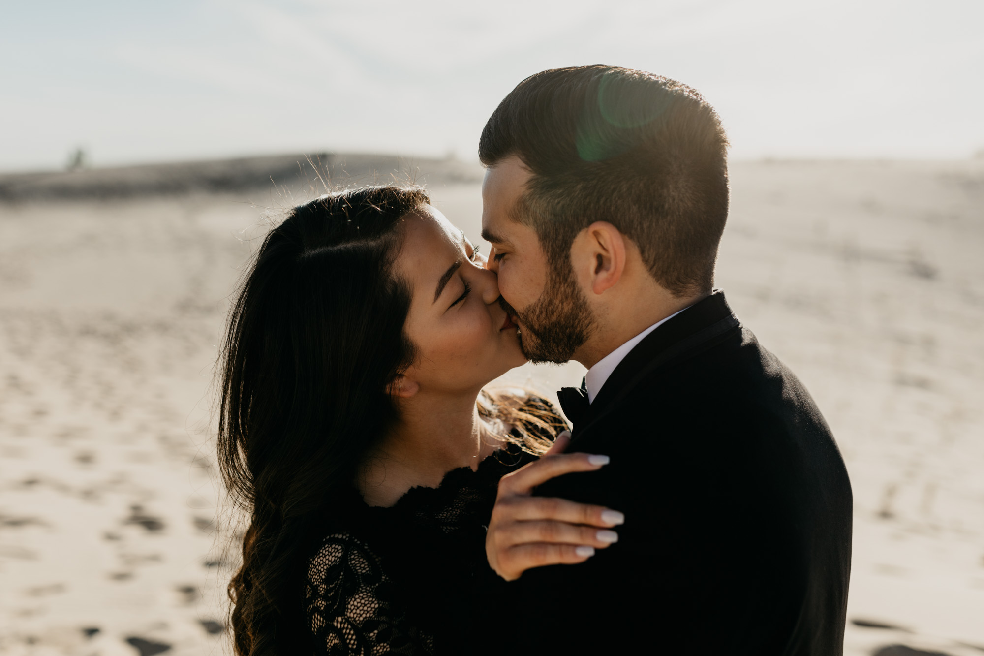Adventurous couple kissing during an engagement session