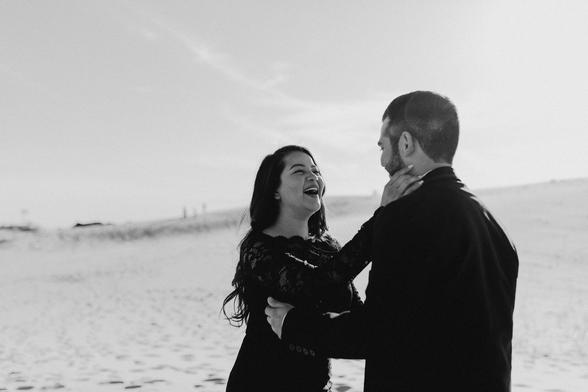 Black and white photo of a playful couple during their sand hills engagement session