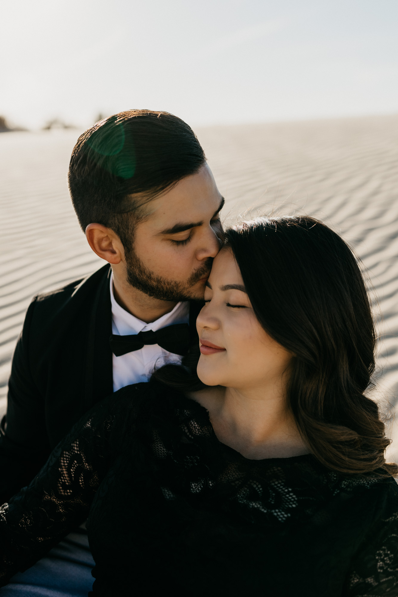 Boy kissing girl on the forehead during a cozy and romantic desert engagement session