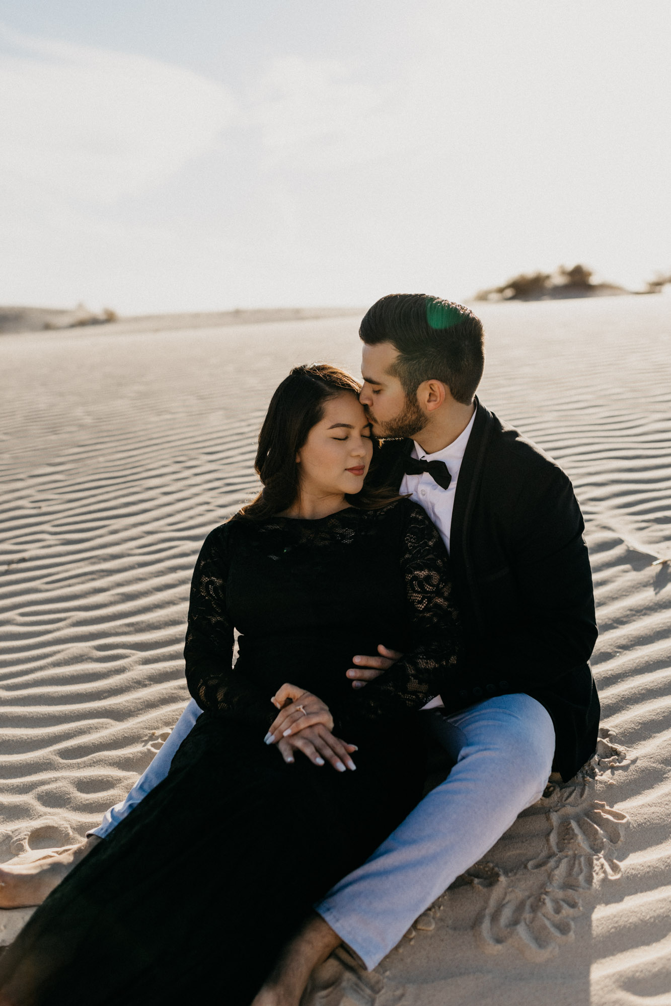 Girl and boy sitting in the sand and being romantic during their sand hills engagement session with a Fort Worth photographer