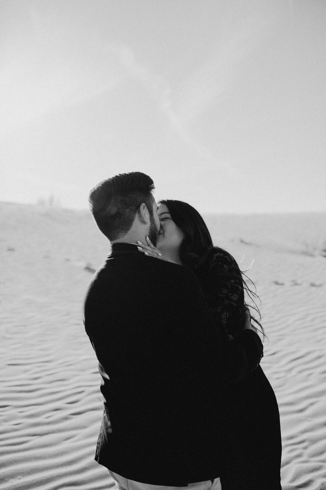 Black and white photo of couple kissing in Sandhills park