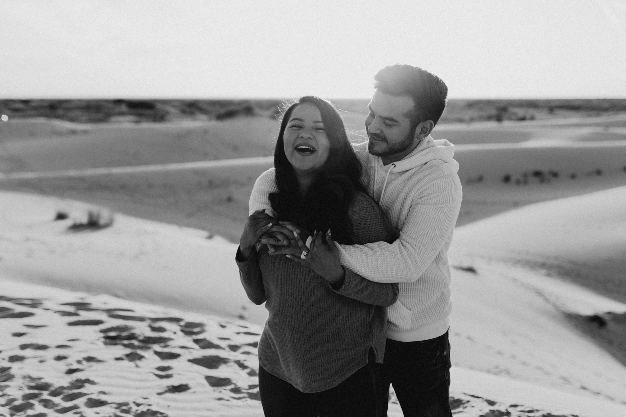 Couple being playful and romantic during their engagement session in west texas at sand hills
