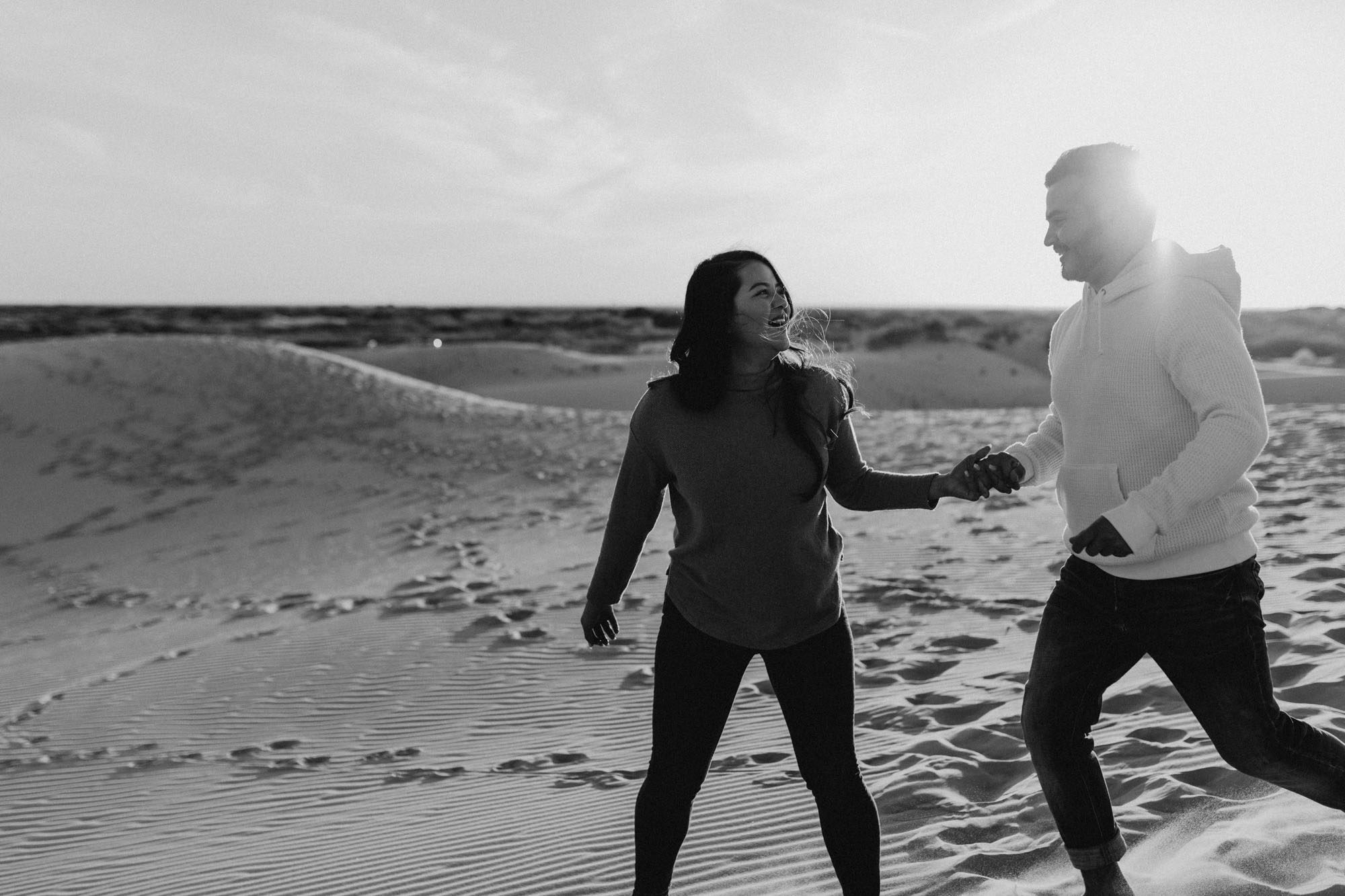 Black and white grainy photo of romantic couple running around during their engagement session
