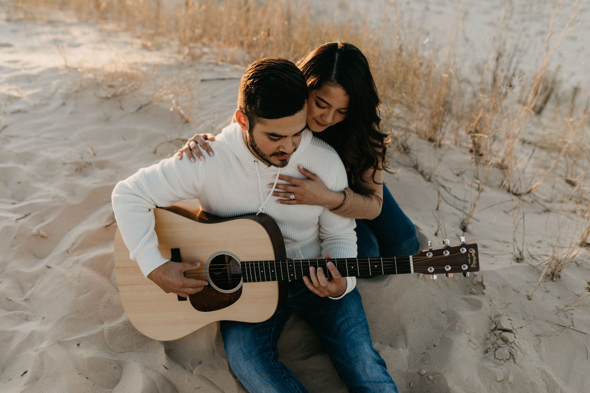 beautiful photo of couple playing the guitar during their engagement session at sand hills