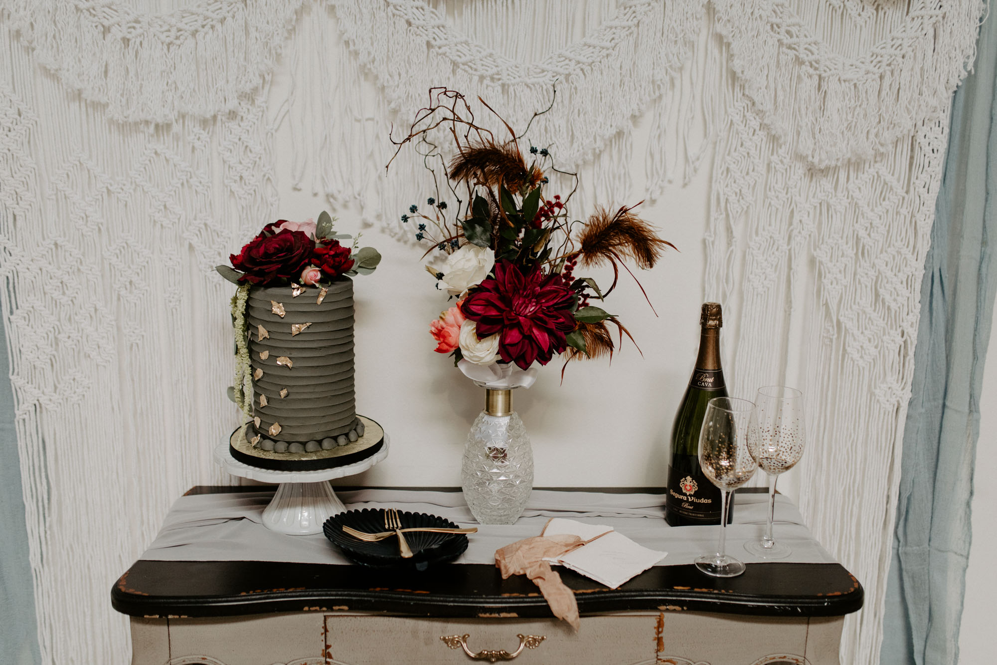 moody cake table with macrame back drop