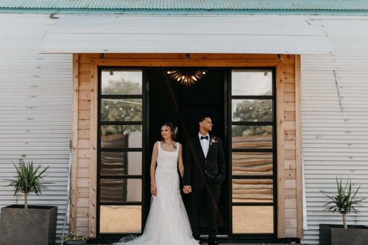 bride and groom standing in doorway looking in opposite directions