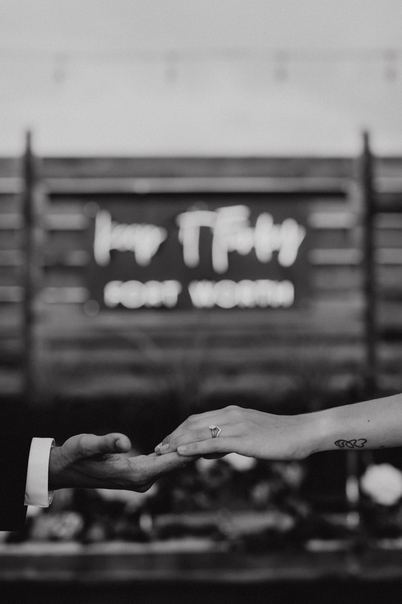 couple touching hands in front of neon wedding sign at moody styled shoot